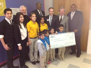 (Image) CEO Doyle Beneby and Board Chairman Derrick Howard present a grant to KIPP Academy as part of the New Energy Economy