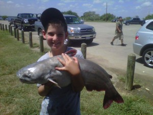 Nine-year-old Patrick Walls shows off the catfish he recently hooked at Calaveras Lake.