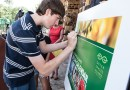 (Image) Douglas Rigdon, 13, signs a display of the new Picture Your World calendar