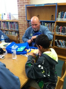 Russ Coons presents his Reading Buddy with his summer backpack filled with books and activities.