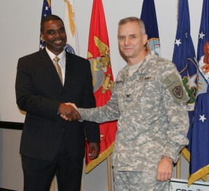 Garrick Williams of CPS Energy, congratulates Col. James Chevallier of JBSA for their committement to saving energy.