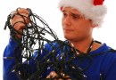 (Image) Man with santa claus hat holding tangled christmas tree lights