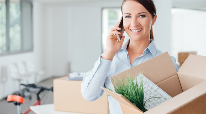 (Image) shutterstock_291771824 woman on mobile phone holding cardboard box