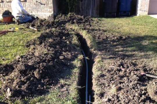 Plumbers lay new water line in a freshly dug trench.