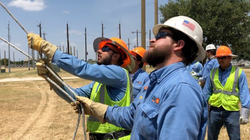 (Image) Interns practice using a handline to safely send up tools to linemen working in bucket trucks.