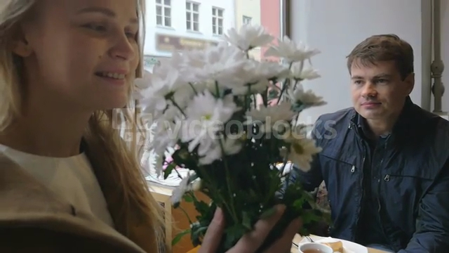 slow-motion-clip-of-a-young-woman-and-man-having-a-date-in-cafe-she-enjoying-the-smell-of-presented-flowers-while-he-looking-at-her-with-love_ekhoxtg4l__PM13-08-14