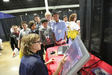 Students standing and watching a computer demonstration
