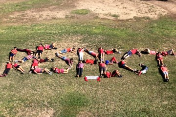 """Students lying in a field, spelling out """"RESPECT."""""""