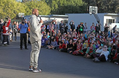 Kobe talks with students at an assembly.