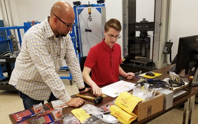 Laboratory technician Tony Figueroa helps El Toro High student Mason Maragon work design an experiment to test the integrity of a pad lock.