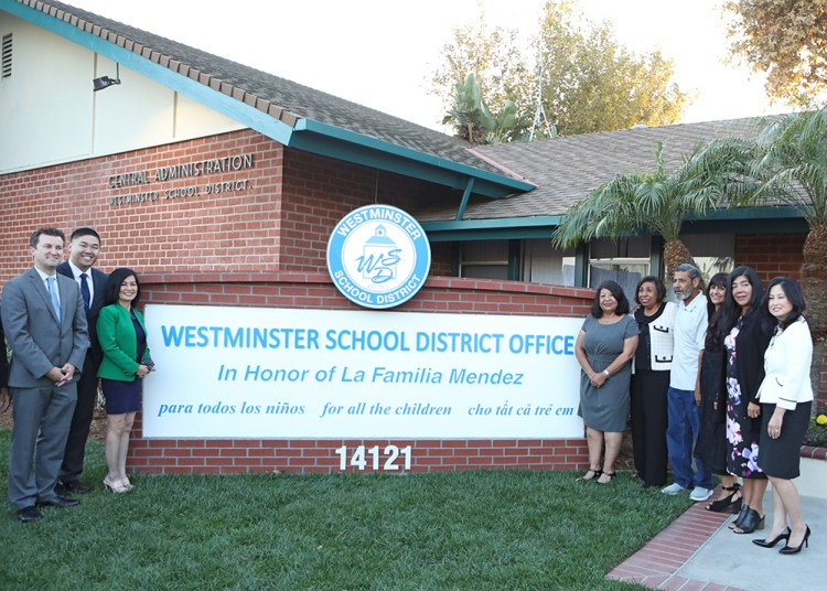 educators and activists stand in front of new dedication sign for school district