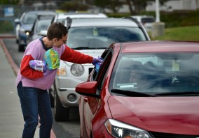School staff handing sack lunch to person in car