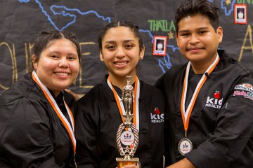 Three high school culinary students with trophy