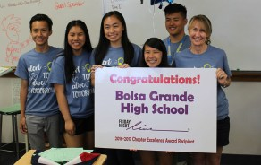 Students from Friday Night Live program hold congratulatory signs