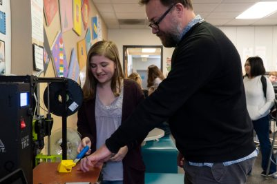 Student and teacher work with a 3D printer