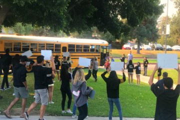 Cheerleaders, ASB leaders and others greet an arriving school bus