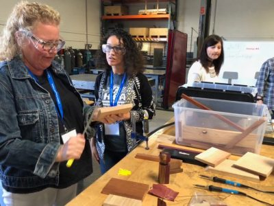 School counselor filing a block of wood with two educators in the background