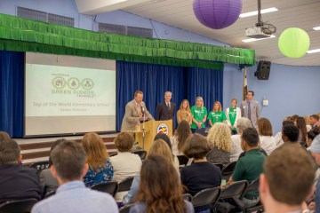 Principal addresses crowd in a multipurpose room