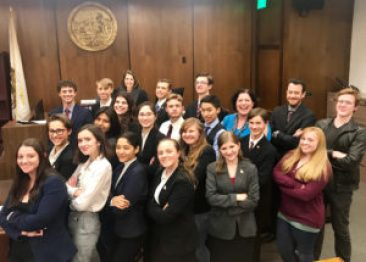 students from mock trial team pose for photo in courtroom
