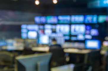 A blurred image of a broadcast newsroom