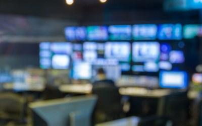 A blurred image of a broadcast newsroom