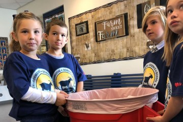 Kids holding a recycle bin