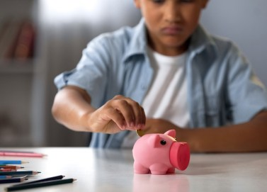 Kid filling piggy bank