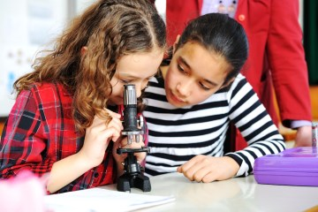 an image of girls using a microscope