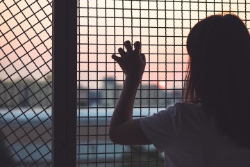 Woman grabbing a fence