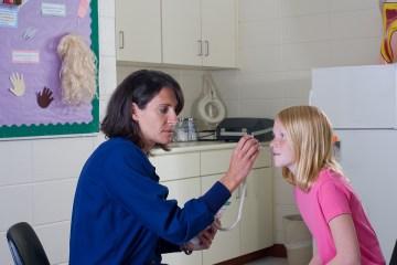 School nurse checking temperature of student patient.