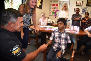 An image of Tustin PD Officer Ralph Casiello and TUSD nurse Pam Atkins greeting 13-year-old Siva Pelluru