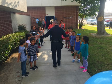 police officer high-fiving students at GGUSD