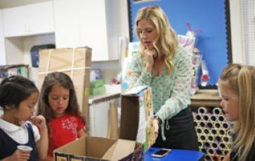 Kindergarten teacher Courtney Smith helps students with their class projects