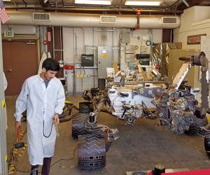 An engineer exams in a lab a scale model of the Mars Curiosity Rover