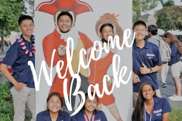 """Oxford Academy students pose with a """"welcome back to school"""" sign"""