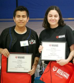 Two students holding awards