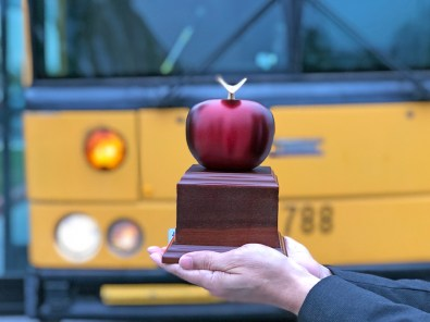 apple trophy in front of a bus