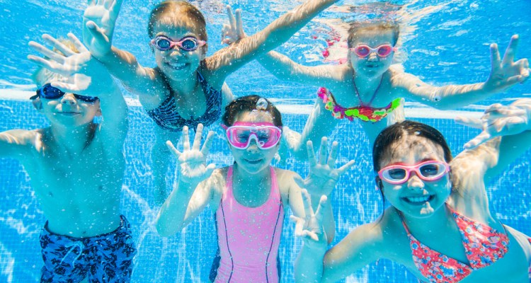 a group of children under water in a swimming pool