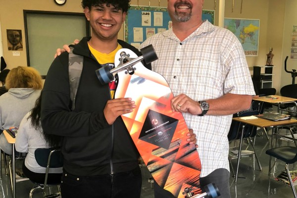 A student and teacher, holding a skateboard
