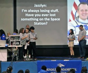 students on stage asking question via audio stream to astronaut