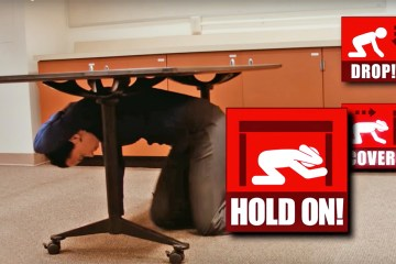 student under desk during earthquake drill