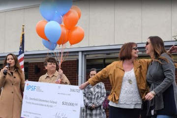 A big check is awarded to a school at an assembly