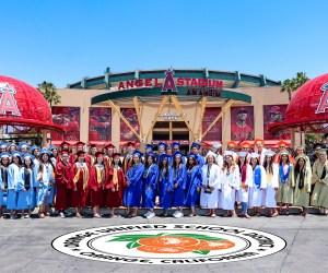 high school grads pose in front of angel stadium