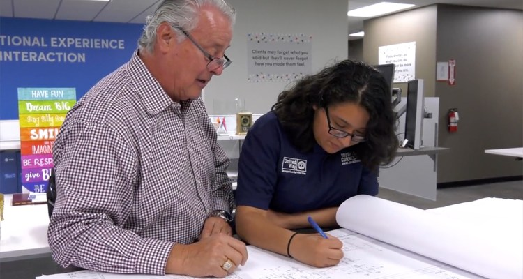 student works with mentor at a desk