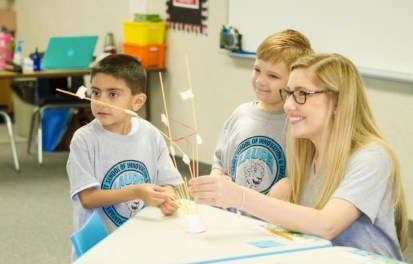 teacher works with students on a project