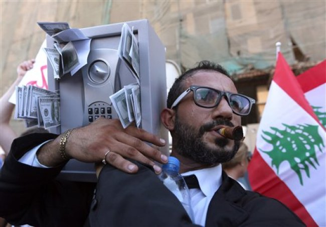 A Lebanese anti-government protester acts the role of a Lebanese politician during a demonstration against the trash crisis and government corruption, in downtown Beirut, Lebanon, Aug. 29, 2015. (AP Photo/Bilal Hussein)