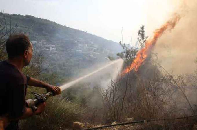 A Lebanese firefighter sprays water in desperate attempt to douse forest fire flames | Source: GettyImages