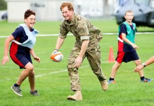 Принц Гарри играл в регби с детьми во время посещения военного лагеря Линтон в Новой Зеландии в мае 2015 года.