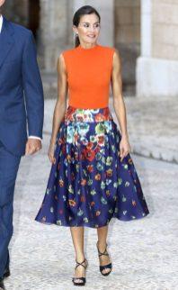 3 августа 2018 На официальный ужин на Майорке, Королева Летиция надела оранжевую трикотажную майку Hugo Boss с синей юбкой Carolina Herrera с цветочным принтом. Завершающий штрих: босоножки Magrit с ремешком из лакированной кожи на заказ.