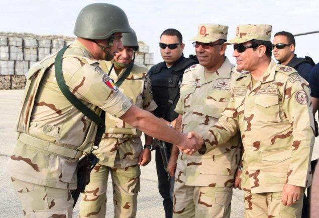 Президент Египта Абдель Фаттах аль-Сиси-(R) приветствует членов египетских вооруженных сил, после путешествия в обеспокоенную северную часть Синайского полуострова, чтобы осмотреть войска, в этом 4 июля 2015 картинная любезность раздаточных материалов египетского Президентства. Вооруженные силы Египта убили 35 исламистских бойцов в Северном Синае в четверг, источники безопасности сказали, спустя день после самых смертельных столкновений в регионе в годах. Источники сказали, что убитые приняли участие в борьбе в среду, в которой армия сказала, что 100 бойцов и 17 солдат были убиты. Источники сказали, что жертвы в четверг включали воинственных полевых командиров. (Египетское Президентство АГЕНТСТВА РЕЙТЕР/)